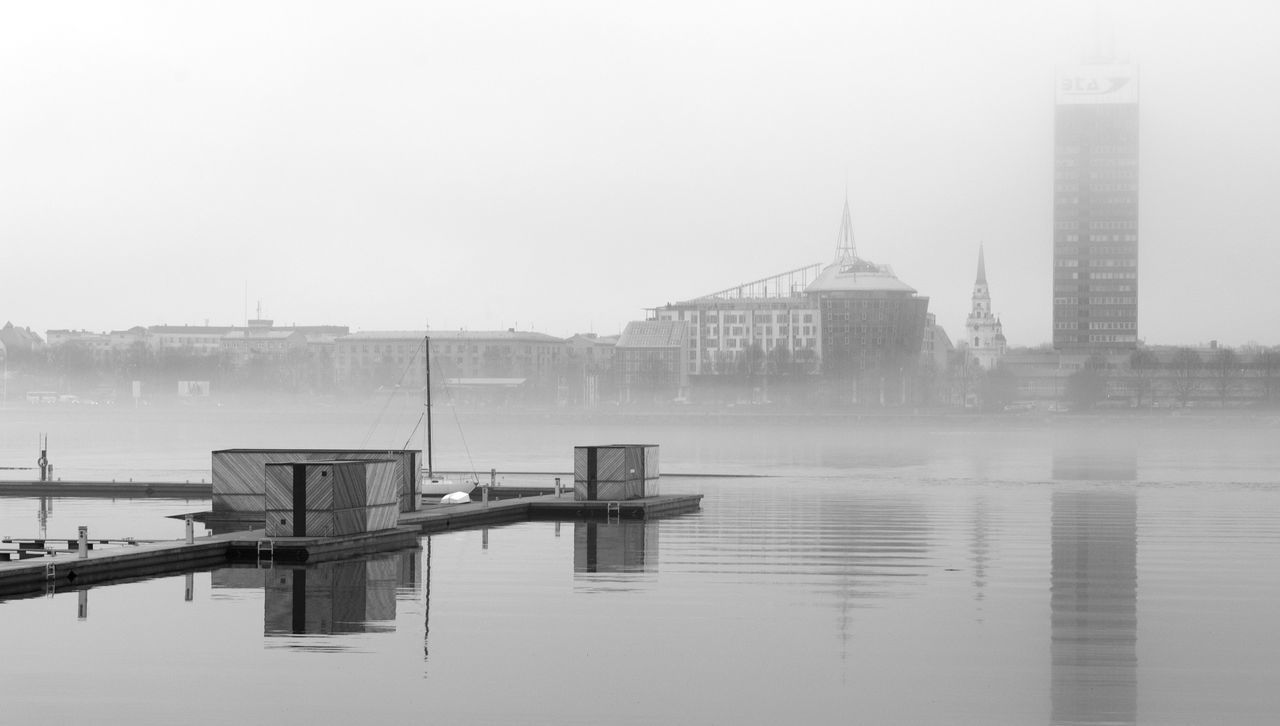 water, architecture, built structure, building exterior, fog, foggy, waterfront, river, city, no people, outdoors, skyscraper, travel destinations, day, winter, nature, sky