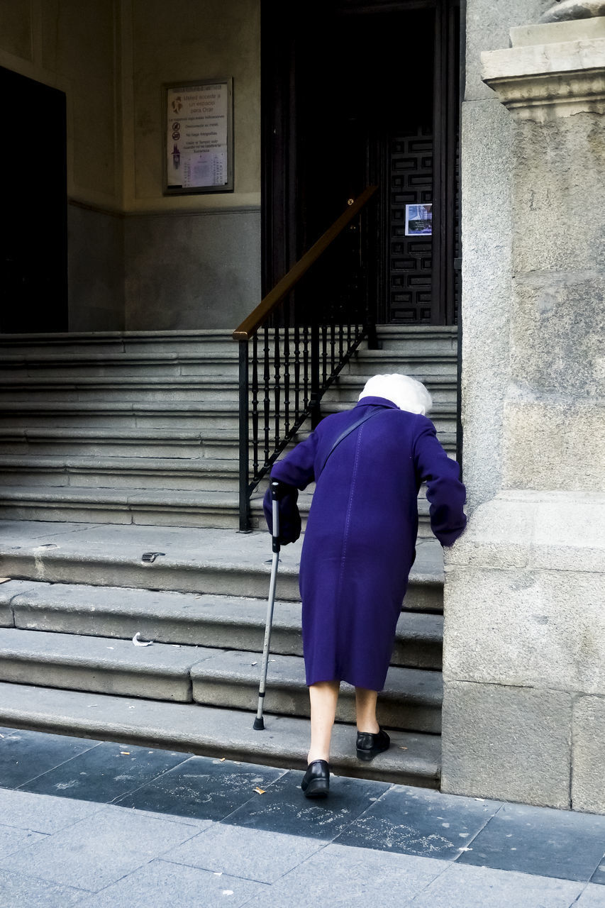 FULL LENGTH REAR VIEW OF WOMAN WALKING ON STAIRCASE OF BUILDING
