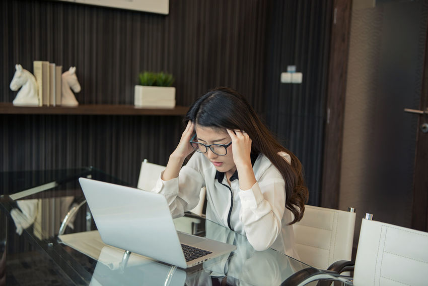 A Stressed Asian business woman using a laptop in office Asian  Office Beautiful Woman Business Business Woman Businesswoman Communication Computer Corporate Business Desk Eyeglasses  Indoors  Laptop Meeting Room Occupation Office One Young Woman Only Sitting Stressed Technology Using Laptop Well-dressed Women Working Young Women