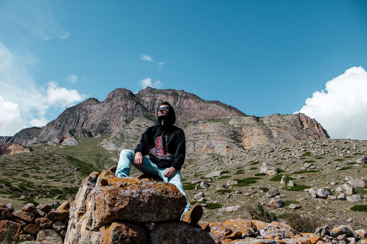 Low angle view of man sitting on rock against mountain
