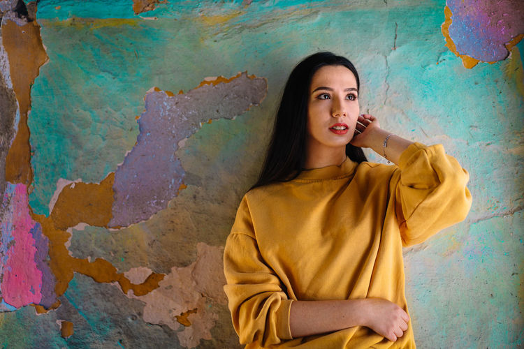 Portrait of beautiful young woman standing against colorful wall