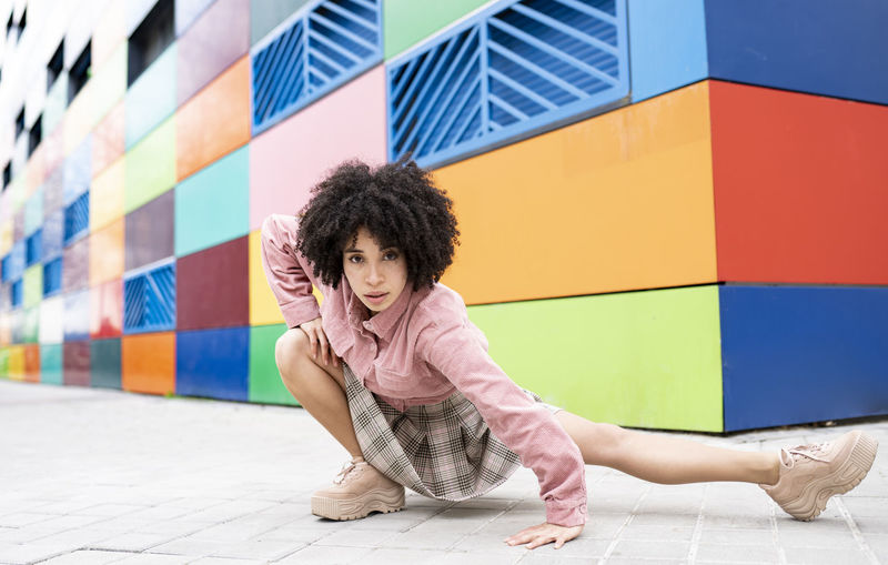 Portrait of woman against multi colored wall