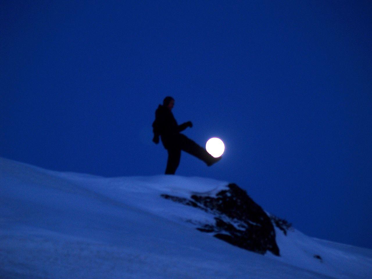 Optical Illusion Of Man Kicking Full Moon Clear Sky At Dusk