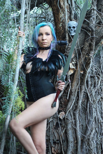 Portrait Of Seductive Woman Holding Sword By Tree In Forest