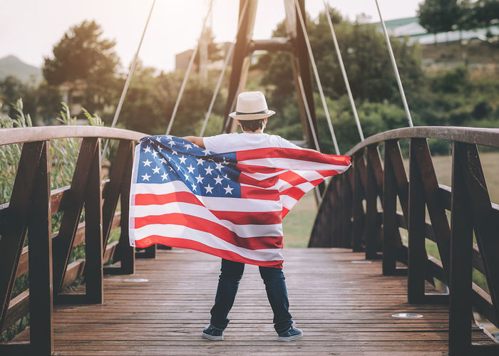 Rear view of boy with american flag standing on bridge