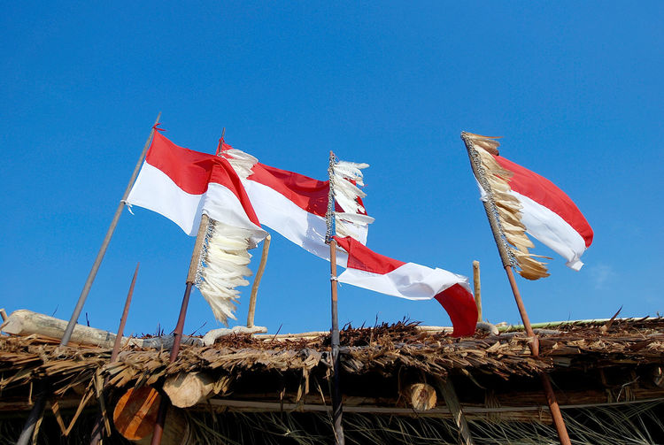 Indonesian flag. Architecture Blue Built Structure Clear Sky Copy Space Day Environment Flag Flags Indonesian Flag Low Angle View Nature No People Outdoors Patriotism Pole Red Roof Sky Sunlight Wind