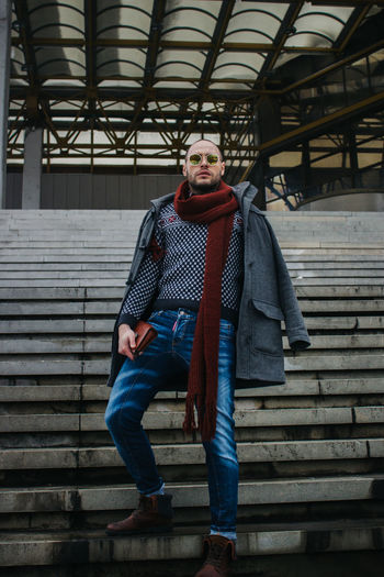Portrait of man wearing warm clothing standing on steps outdoors