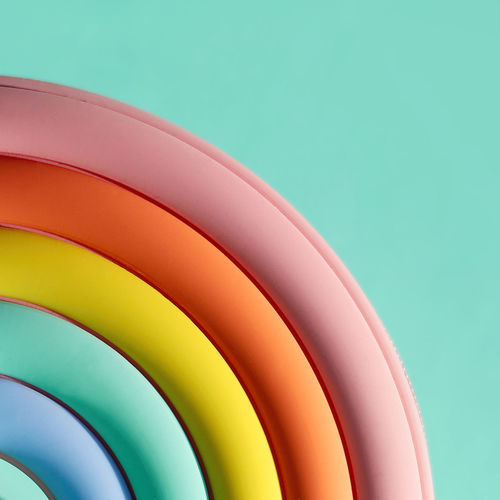 A fragment of a handbag in the form of a bright rainbow on a green background. close-up