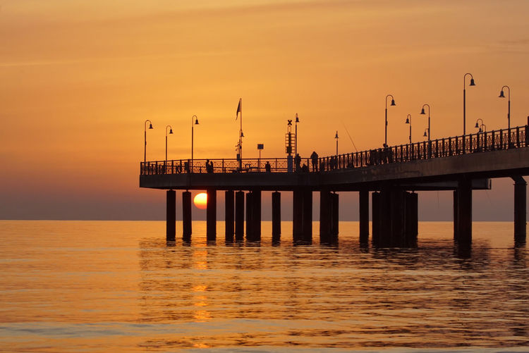 Pier in the sunset with streetlights