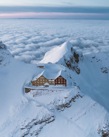 Aerial view of snow covered land and building against sky