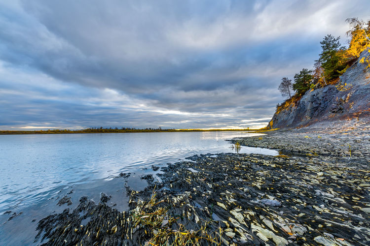 Autumn evening at the stony bank of the Siberian river Beauty In Nature Cloud - Sky Nature No People Non-urban Scene River, Evening Rock Scenics - Nature Sky Solid Tranquil Scene Tranquility Water