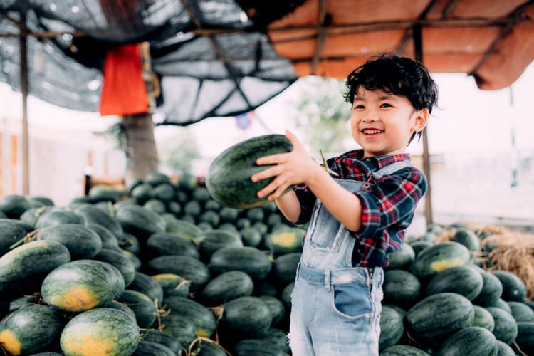 Smiling boy holding watermelons while standing outdoors
