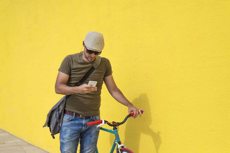 Man using mobile phone while standing with bicycle by yellow wall