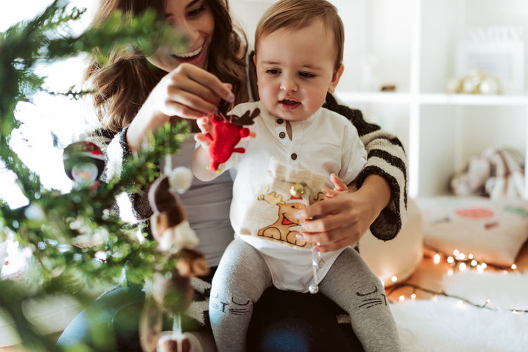 Cute girl holding christmas tree at home