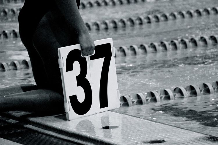 Midsection of woman holding number 37 while kneeling at pool