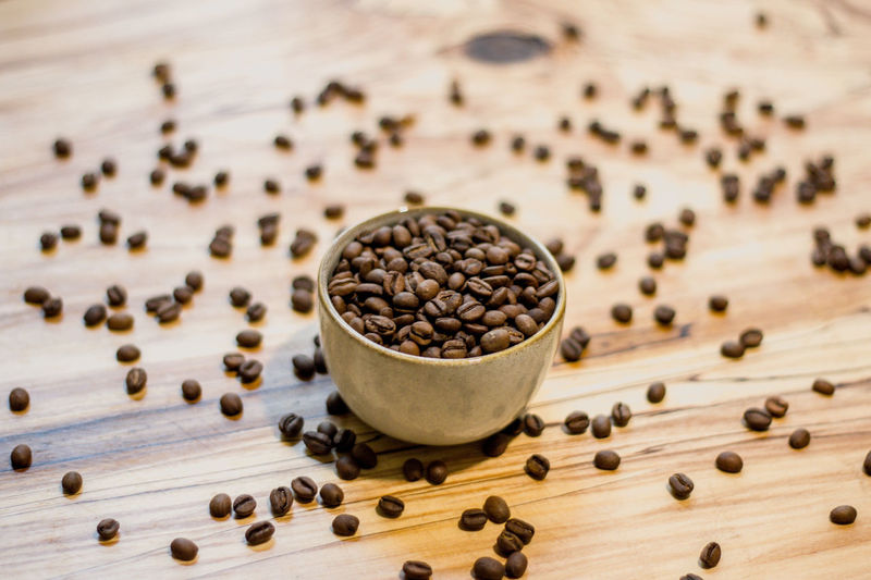 Food And Drink Freshness Wood - Material Food Roasted Coffee Bean Table Large Group Of Objects No People Brown Close-up Abundance Indoors  High Angle View Raw Food Seed Coffee Coffee - Drink Still Life Focus On Foreground Roasted Caffeine