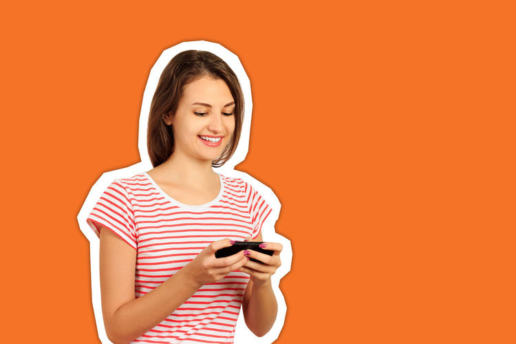 Portrait of smiling young woman using smart phone against orange background