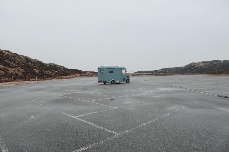 Van at parking lot against sky