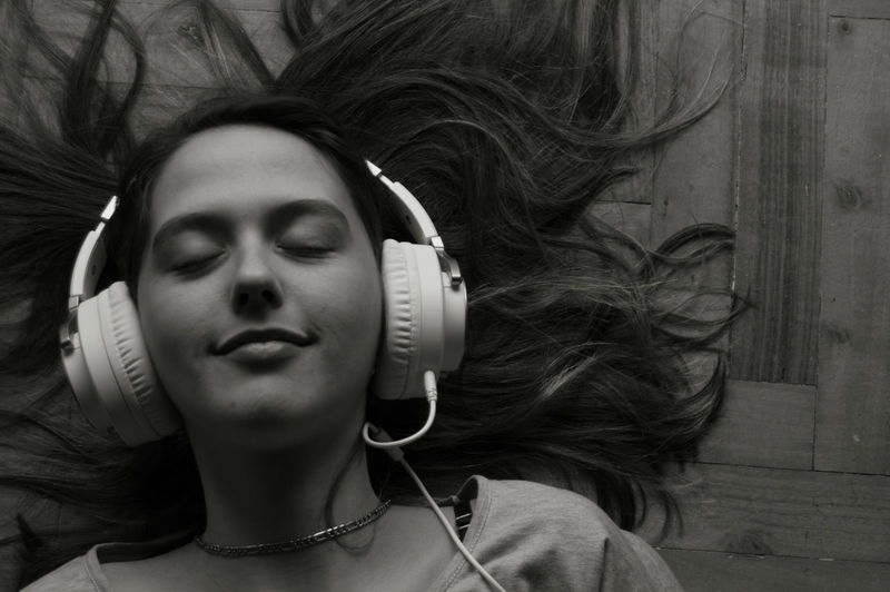 Close-Up Of Woman Listening Music While Lying On Hardwood Floor
