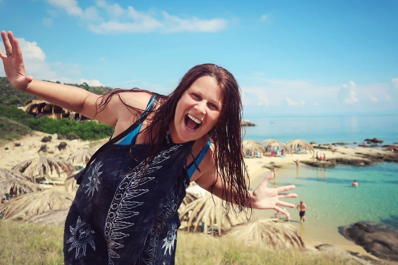 Portrait of happy woman screaming while standing at beach