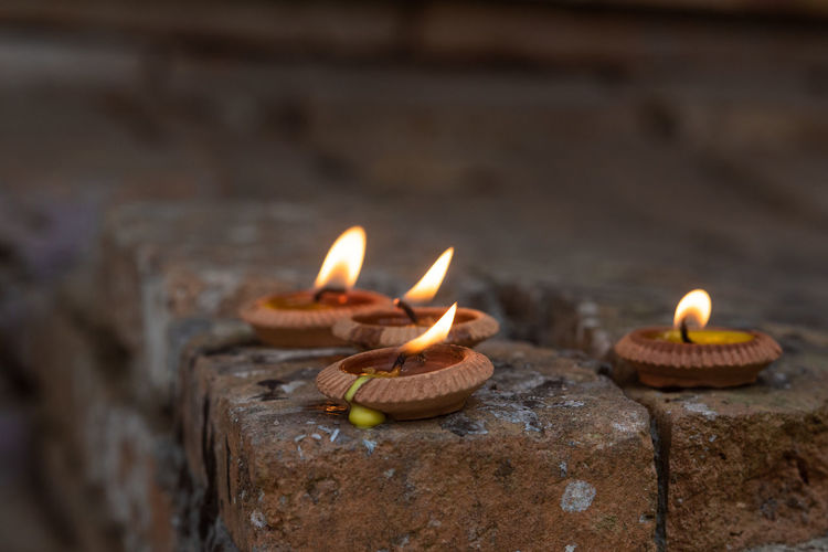 Belief Burning Candle Celebration Close-up Diya - Oil Lamp Electric Lamp Fire Fire - Natural Phenomenon Flame Glowing Heat - Temperature Illuminated Lighting Equipment Nature No People Oil Lamp Outdoors Selective Focus
