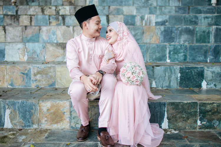 Full length of couple standing against pink wall