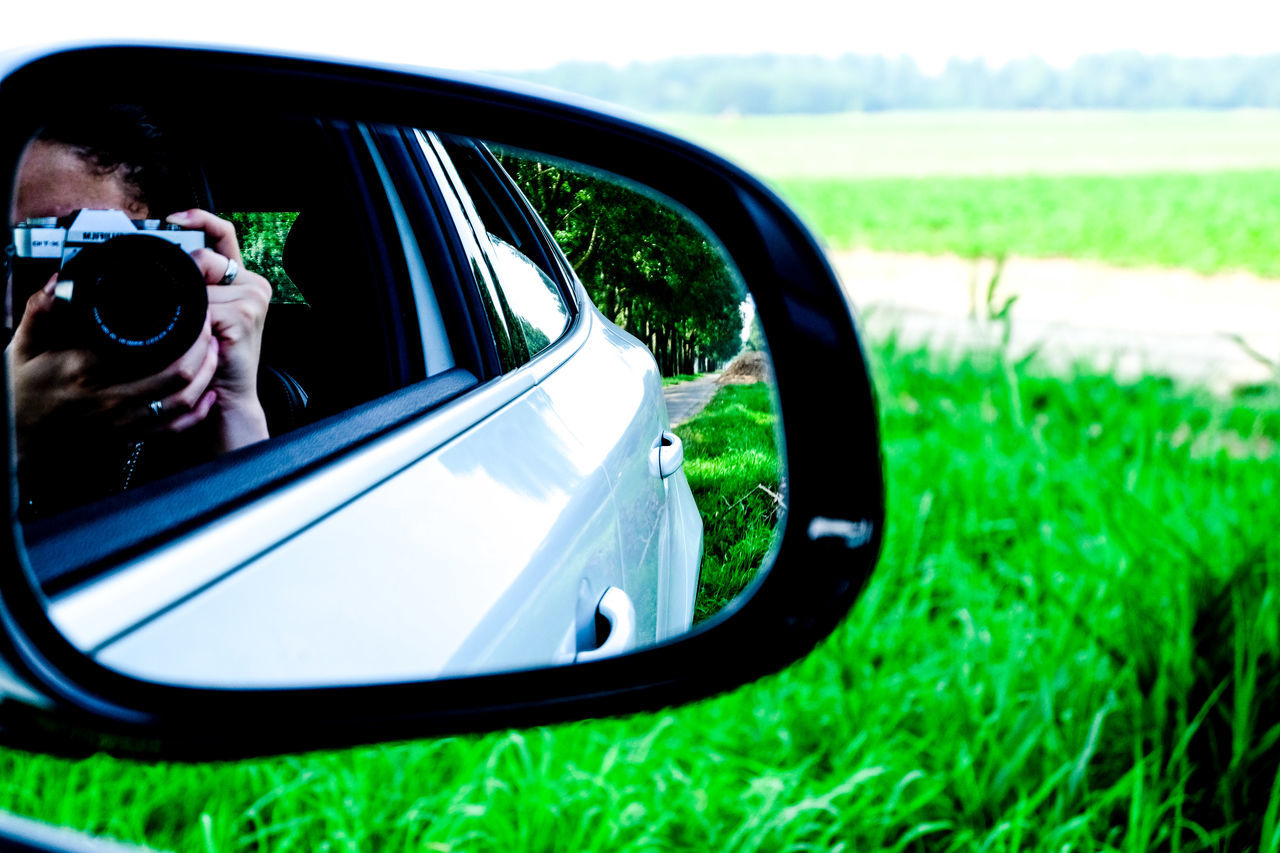Reflection Of Person Photographing In Side-view Mirror