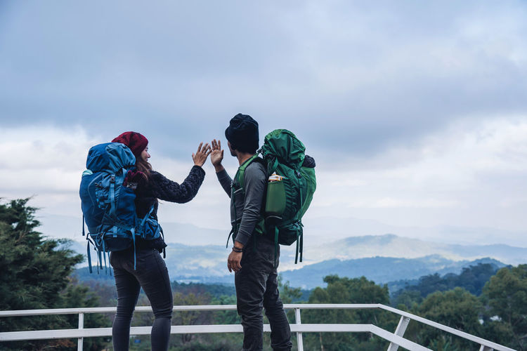 Couple standing against mountains at observation point