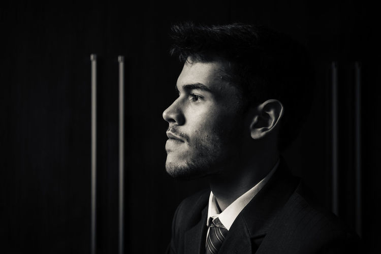 Close-Up Of Man Looking Away Against Black Background