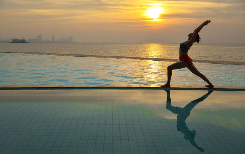 Woman in swimming pool against sea during sunset