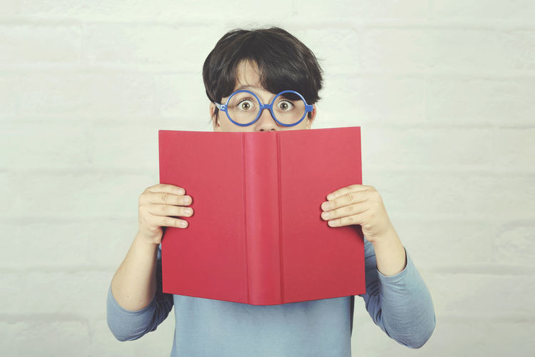 Holding Portrait Looking At Camera Standing Child Childhood Book Education Wisdom Surprised Learning Learn Study Studying Study Time Student School Schoolboy Lifestyle Reading Reading A Book Fun Glasses Concept Lesson Homework Ready Genius Educational Intelligence Intelligent Happy Happiness Expression Emotion Inspiration Idea Textbook Cute People Playing Class Laughing