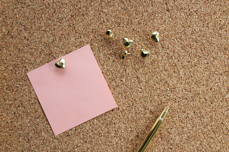 Close-up of adhesive note with pen on bulletin board