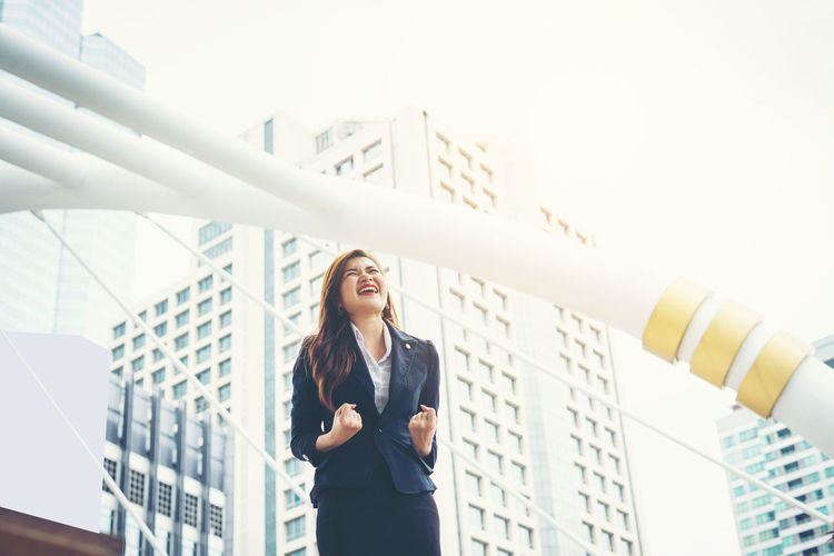 Low angle view of happy businesswoman clenching fists against buildings in city