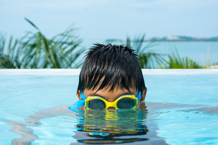 Portrait of boy swimming in pool against sky