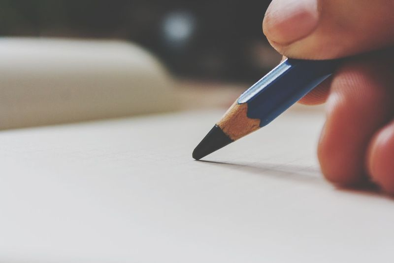 Close-Up Of Person Writing With Pencil