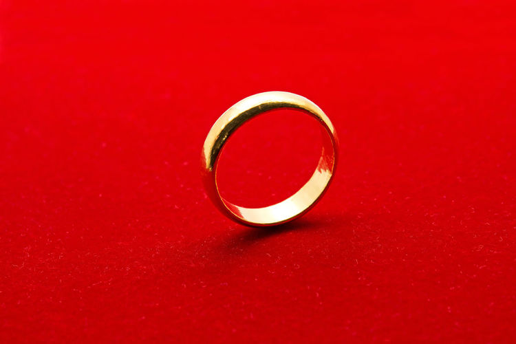 Close-up of wedding rings on red table