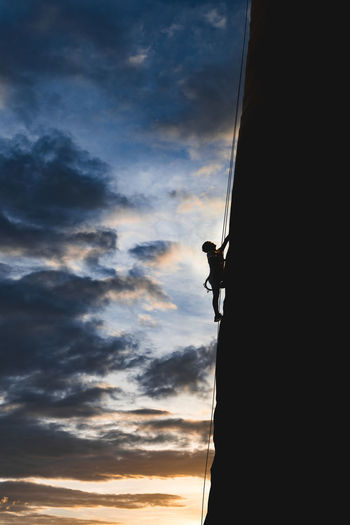 Low Angle View Of Silhouette Man Rock Climbing Against Sky