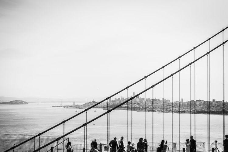 Group of people on bridge over sea