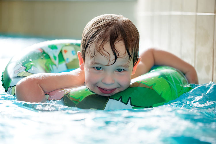 Portrait Of Happy Boy Swimming With Inflatable Ring In Pool