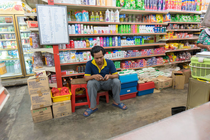 A man who working in grocery shop take five, sitting. Buying Parts Sale Shopping Supermarket Work Business Finance And Industry Customer  Day Display Indoors  Job Lifestyles Men People Purchase Real People Retail  Scenics Sell Shelf Trade
