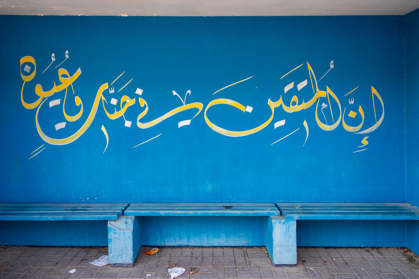 Bus stop in Bahrain, Kingdom of Bahrain. Arabic Script Bahrain Kingdom Of Bahrain Architecture Art And Craft Blue Built Structure Bus Stop Communication Creativity Day Graffiti Mural Nature No People Outdoors Sky Street Art Text Turquoise Colored Wall - Building Feature Western Script Wood - Material Yellow