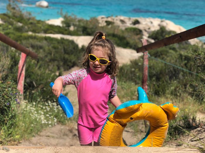 Girl wearing sunglasses while holding inflatable ring and toy at beach