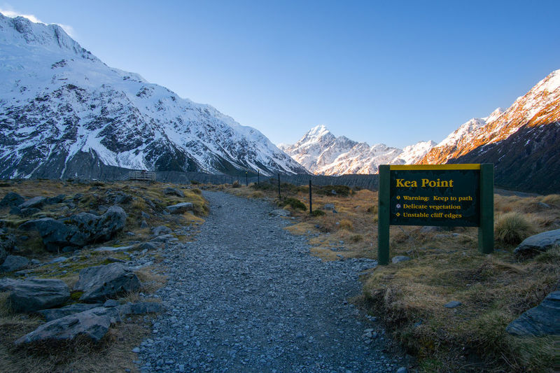 Walking trek to Kea Point with Mount Cook in the background Mountain Communication Text Sign Winter Scenics - Nature Beauty In Nature Cold Temperature Snow Mountain Range Sky Nature Information Environment Western Script Tranquility Tranquil Scene Snowcapped Mountain No People Mountain Peak
