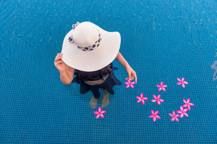 Summer Vacation Plumeria Woman Blue Clothing Day Directly Above Flower Hat High Angle View Holiday Leisure Activity Nature One Person Outdoors Pool Real People Sun Hat Sunhat Swimming Pool Top View Water