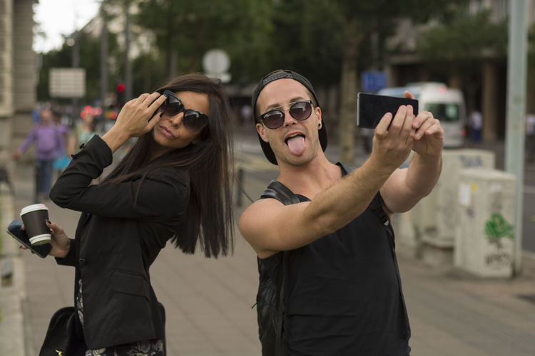 Young couple taking selfie on street through mobile phone