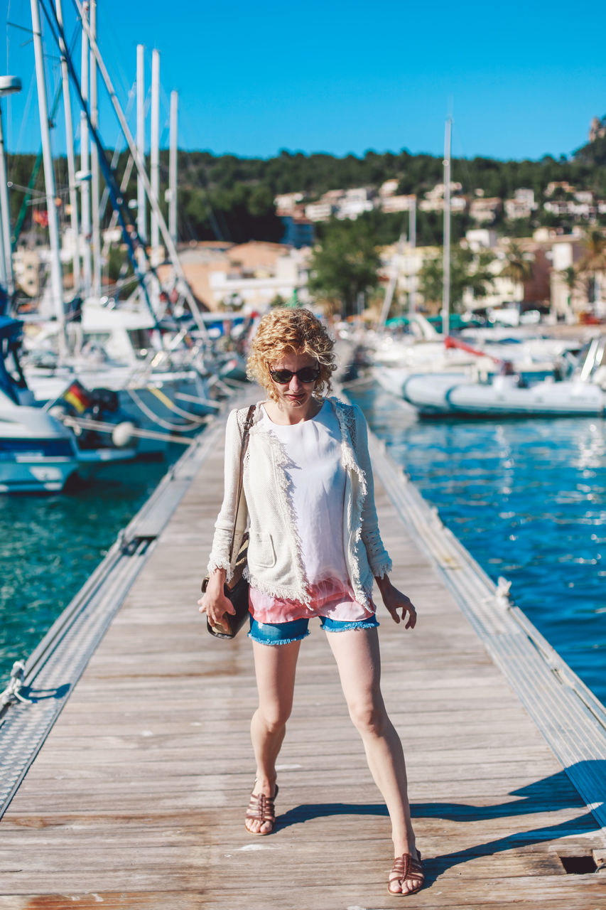 water, nautical vessel, pier, real people, full length, one person, harbor, sea, day, jetty, mode of transport, leisure activity, outdoors, front view, moored, sunlight, transportation, casual clothing, young adult, sailboat, lifestyles, young women, yacht, nature, blond hair, clear sky, sky, people