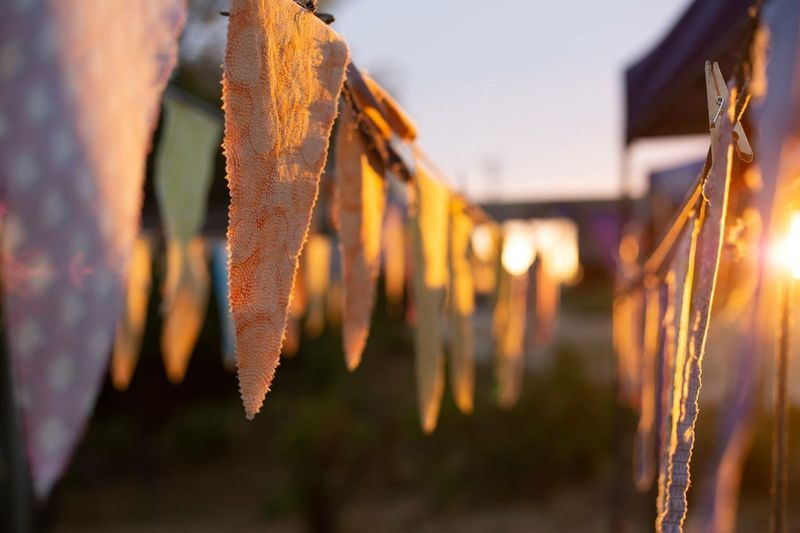 Close-up of clothes drying against sky during sunset