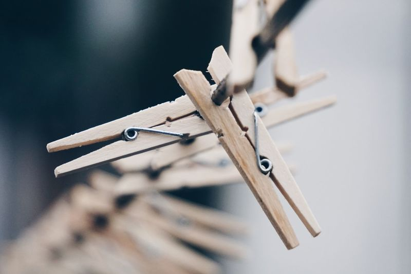 Close-up of clothespins on rope outdoors