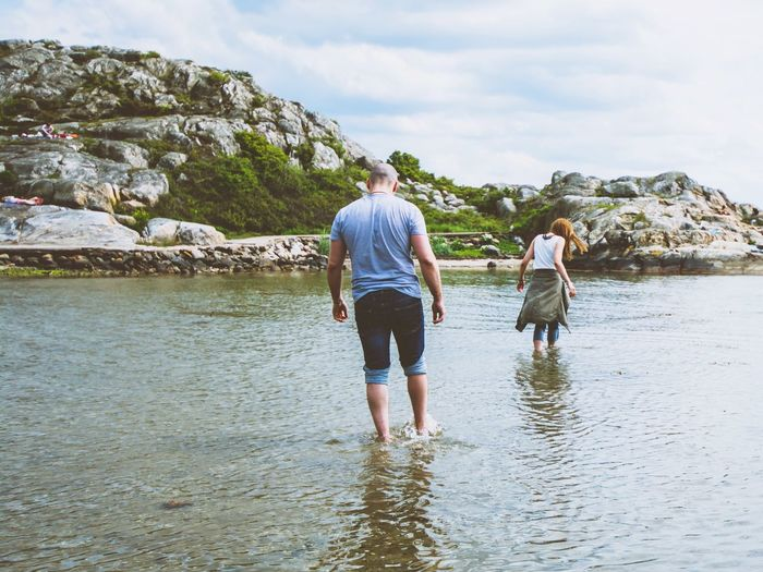 Rear View Of Couple Walking Through Shallow Water