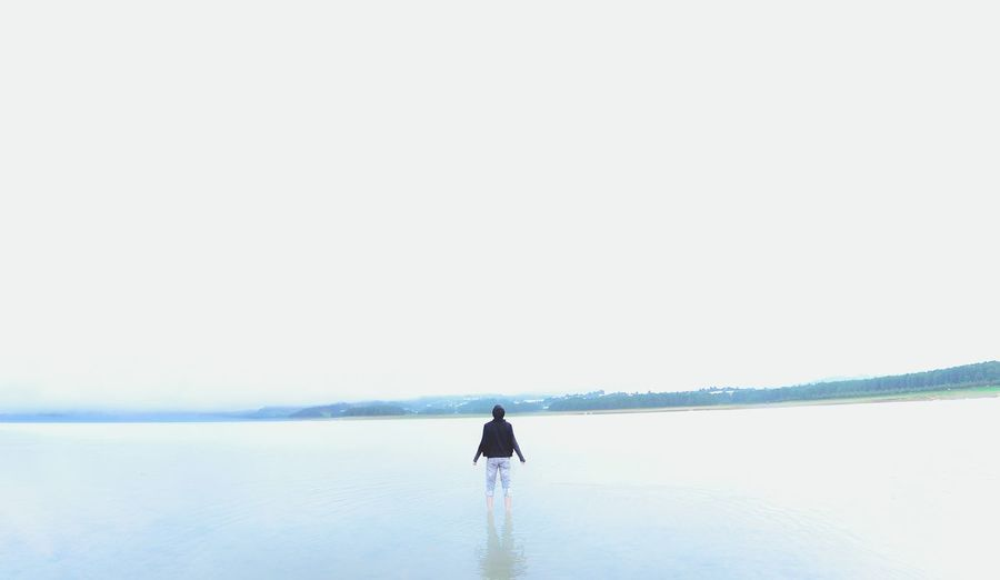 Rear view of man standing in calm lake